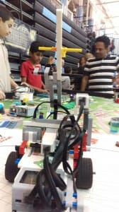 Skyler Silva, 10, (in red), explores Transformers robots at the City of Science while his father (right) looks on.