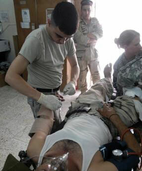 Ruiz treating an injured soldier at a facility in Iraq.