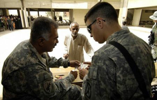 Justin Ruiz, right, confers with an Army colleague during his tour in Iraq.